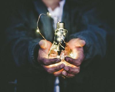 Holding lightbulb.